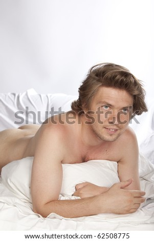 Portrait of a nude young man lying in bed. He could be watching tv. Studio shot. See more in my portfolio - stock photo