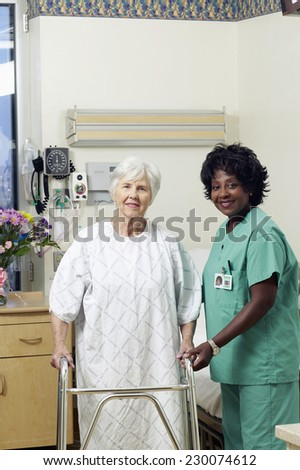 Portrait of a nurse helping an aging lady walk with a walker - stock photo