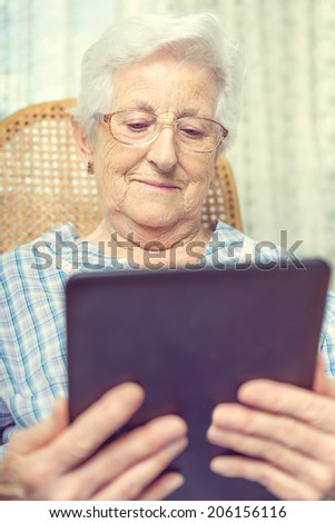 Portrait of a old woman smiling happily as she reads the screen on her tablet computer