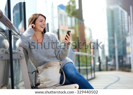 Portrait of a older woman smiling and looking at mobile phone - stock photo