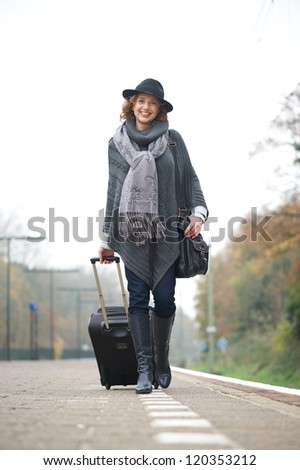Portrait of a older woman walking on train platform with bag - stock photo