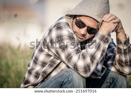 Portrait of a one sad man in sunglasses sitting near the house at the day time - stock photo