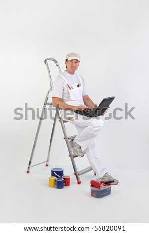 Portrait of a painter leaning on a ladder with a laptop computer - stock photo