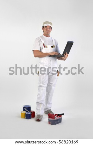 Portrait of a painter with a laptop computer on white background - stock photo