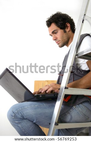 Portrait of a parquet layer sitting on a ladder in front of a laptop computer - stock photo