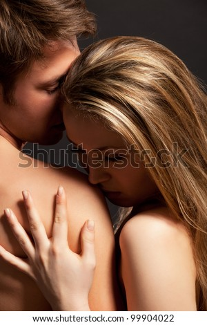 Portrait of a passionate couple, over grey background - stock photo