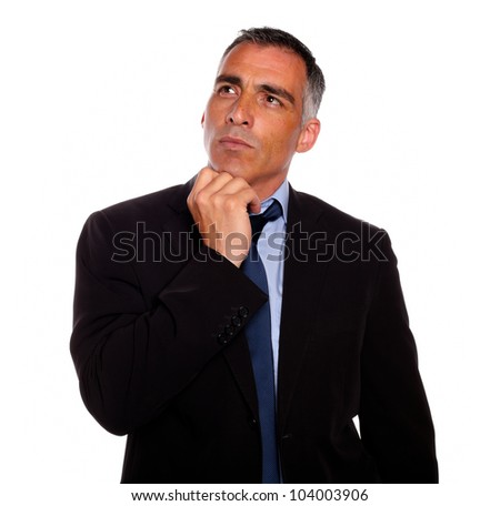 Portrait of a peaceful and reflective man touching the chin while thinking on black suit on isolated background - stock photo