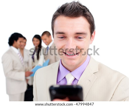 Portrait of a pensive businessman looking at his cellphone in front of his team - stock photo