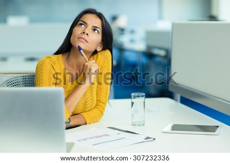 Portrait of a pensive businesswoman sitting at her workplace in office and looking up - stock photo