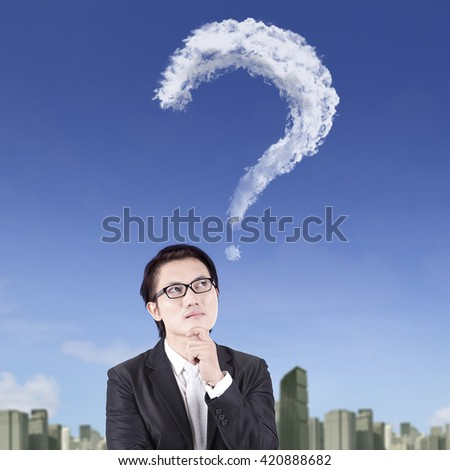 Portrait of a pensive chinese businessman looking at a question mark on the sky - stock photo