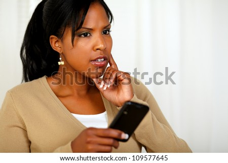 Portrait of a pensive young woman using her cellphone at soft colors composition
