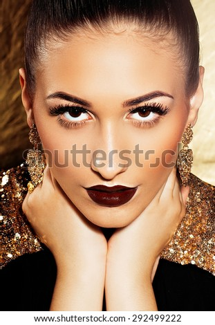 Portrait of a perfect brunette with burgundy lipstick and hands near face