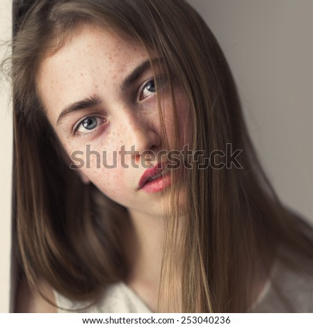 portrait of a perfect girl with freckles closeup home - stock photo
