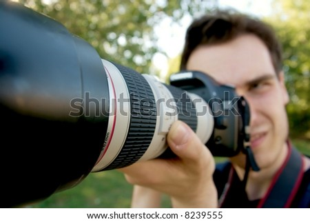 Portrait of a photographer taking pictures with a telephoto lens - stock photo