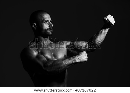 Portrait Of A Physically Fit Man Showing His Well Trained Body In Dark Room