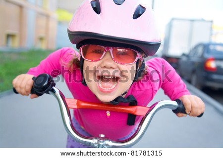 Portrait of a playful funny girl in a pink safety helmet on her bike - stock photo
