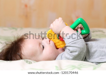 Portrait of a playing baby lying down on back