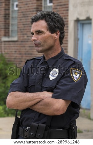Portrait of a police officer, arms crossed, sideways shot - stock photo