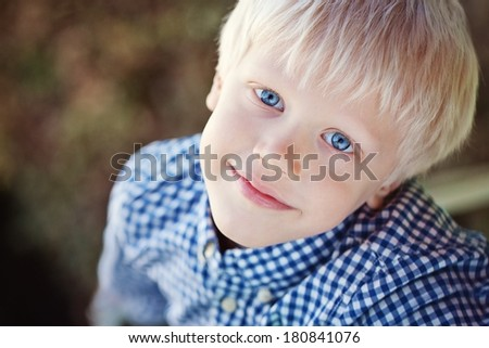 Portrait of a positive little boy (6 years) with a beautiful blue eyes outdoor. - stock photo