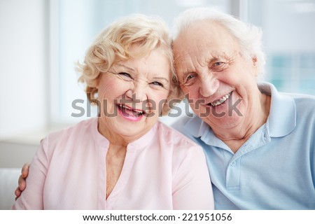 Portrait of a positive senior couple looking at camera and smiling - stock photo
