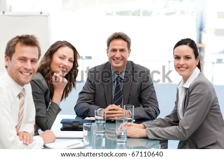 Portrait of a positive team sitting at a table