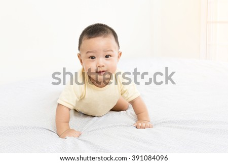 Portrait of a practice crawling baby on the bed in his room - stock photo