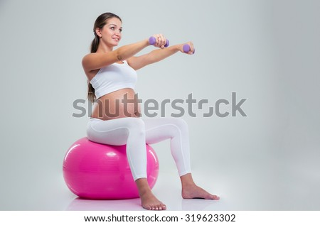 Portrait of a pregnant woman doing exercises with dumbbells on a fitness ball isolated on a white background - stock photo