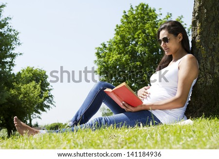 Portrait of a Pregnant Woman Reading under a Tree - stock photo