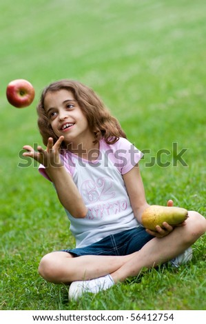 Portrait of a preteen girl trowing apple in the air and with a plum in her other hand and green grass in the background - stock photo