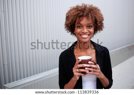 portrait of a pretty African American executive holding a mug - stock photo