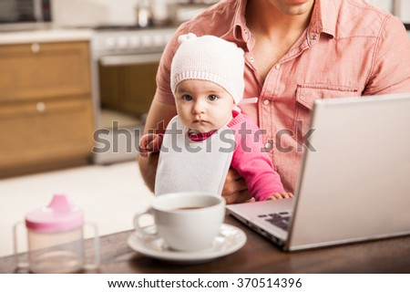 Portrait of a pretty baby girl sitting on her dad's lap while he works at home - stock photo