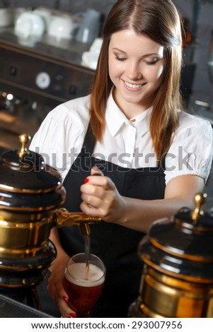 Portrait of a pretty bartender standing smiling and pouring beer, shelves full of bottles with alcohol on the background