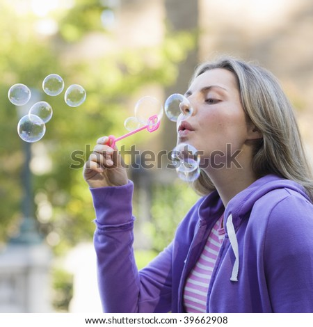 Portrait of a Pretty Blond Teen Girl Blowing Bubbles