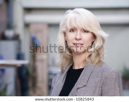 Portrait of a pretty blonde woman in an urban setting - stock photo