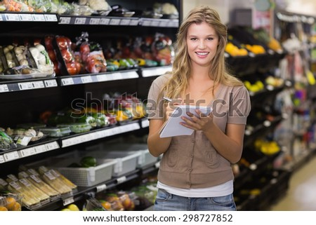 Portrait of a pretty blonde woman writing on notepad at supermarket