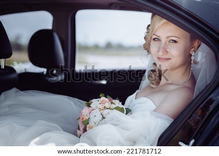 Portrait of a pretty bride in a car.  close-up portrait of a pretty shy bride in a car window. - stock photo