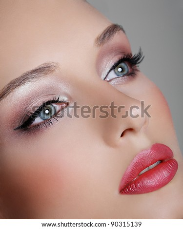Portrait of a pretty brunette girl with blue eyes, closeup - stock photo
