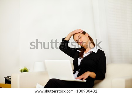 Portrait of a pretty business woman working at home with neck pain - stock photo