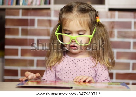 Portrait of a pretty child girl in funny green eyeglasses sitting at the desk and reading a book, indoor education concept - stock photo