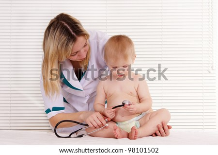 portrait of a pretty doctor with baby - stock photo