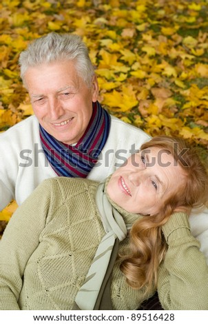 portrait of a pretty elderly couple at autumn forest
