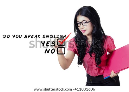 Portrait of a pretty female english teacher writing on the whiteboard while holding folder and wearing glasses - stock photo
