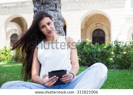 Portrait of a pretty female student reading digital e-book on touch pad at campus, beautiful latin woman holding her tablet computer while posing for the camera during rest after walking in summer day - stock photo