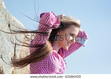 Portrait of a pretty girl at a stone coast - stock photo