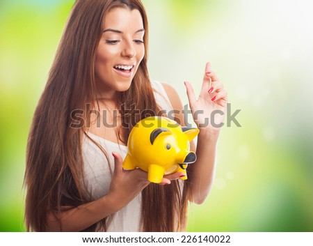 portrait of a pretty girl inserting coin in a piggy bank - stock photo