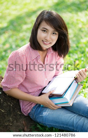 Portrait of a pretty girl studying outdoors - stock photo