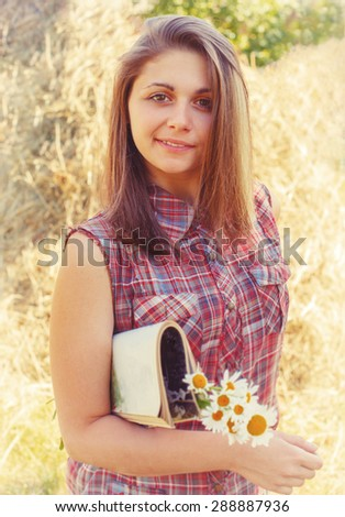 portrait of a pretty girl with a magazine and a bouquet of daisies on a background of haystacks