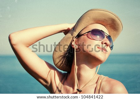 Portrait of a pretty happy young woman enjoying at a beach. Vintage photo - stock photo