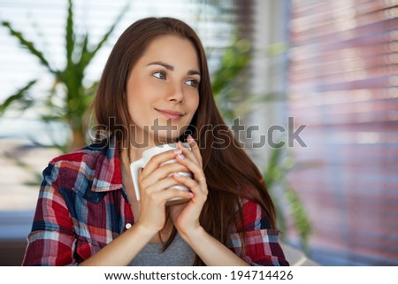 Portrait of a pretty happy young woman holding a cup of coffee - stock photo