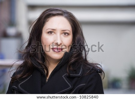 Portrait of a pretty Hispanic woman in an urban setting - stock photo